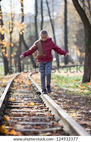 Girl balances on the rail in autumn park - stock photo