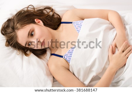 girl became a woman concept - young girl lying with period pain - stock photo