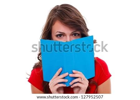 Girl behind colorful book, studio shot - stock photo