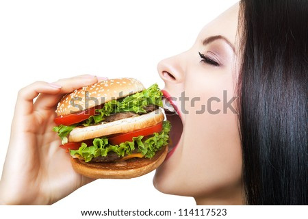 girl biting hamburger with widely opened mouth on white background - stock photo