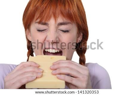 Girl biting piece of cheese - stock photo