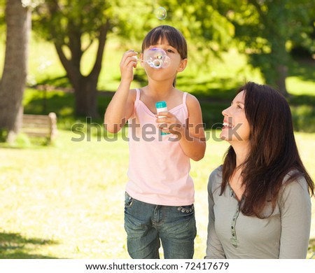Girl blowing bubbles with her mother in the park - stock photo