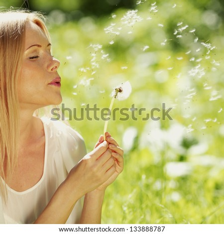 girl blowing on a dandelion lying on the grass - stock photo