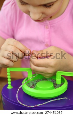 Girl bowing head collects shallow color beads - stock photo