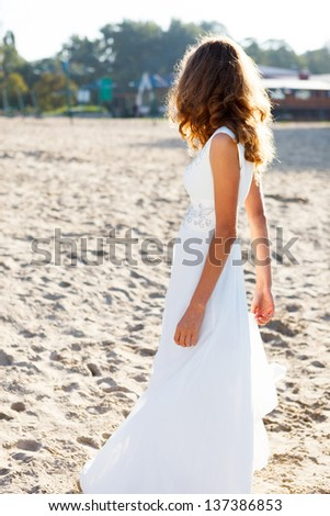 Girl bride in a white dress on the sunny beach half-turned to us. Outdoor - stock photo