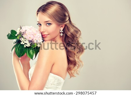 Girl bride  in wedding dress with elegant hairstyle and with a wedding bouquet - stock photo