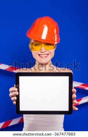 girl builder in the construction helmet and protective glasses on a blue background with the protective tape holding plate, selective focus on the tablet - stock photo