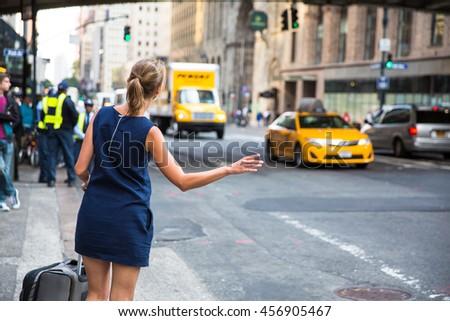 Girl calling/hailking taxi cab on Manhattan, New York City, USA - stock photo
