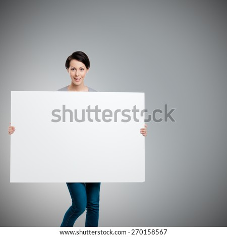 Girl carries a huge sheet of white cardboard , isolated on grey - stock photo