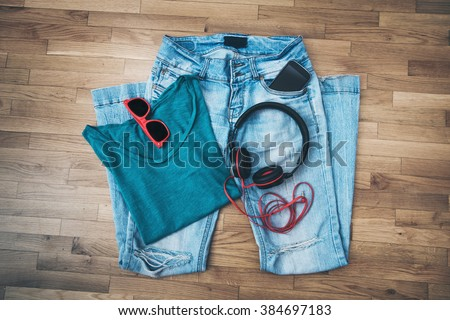 girl casual every day outfit, worn blue jeans, t-shirt, sunglasses, smart phone and headphones - stock photo