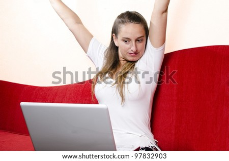 Girl celebrates in front of her laptop. Shot on red couch at living room - stock photo