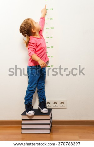 Girl checking height on growth chart at four books - stock photo