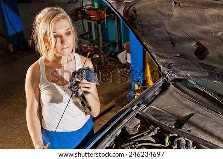 Girl checks the oil level in their own broken car - stock photo