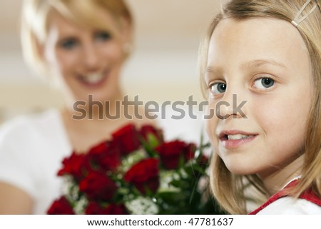 Girl child giving flowers to her mother for mother's day, a bunch of red roses - stock photo