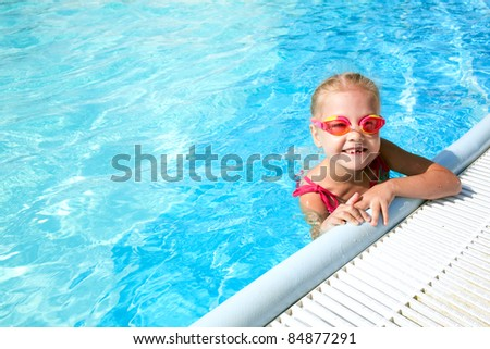 girl child in blue water of the swimming pool - stock photo