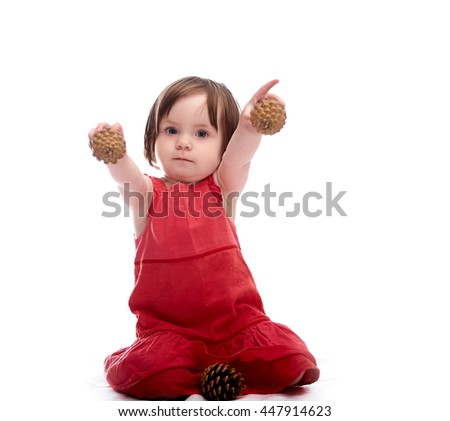 Girl child in red dress isolated on a white background playing with cones - stock photo
