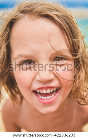 Girl child is looking at the camera and laughing, on summer day on a sandy tropical beach - seaside. Friends, family and children concept. - stock photo