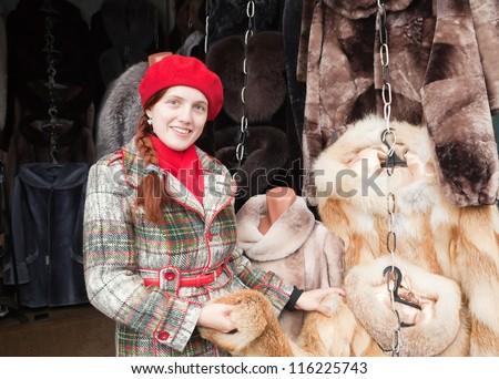 girl chooses a fur coat at market - stock photo