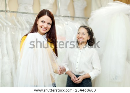 Girl chooses bridal veil at shop of wedding fashion. Friendly shop consultant helps her - stock photo