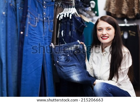 Girl choosing trousers at clothing market - stock photo