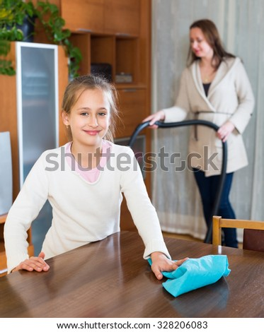 Girl cleaning a table helping her mother to do the cleanup - stock photo