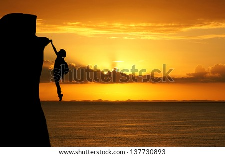 Girl climbing a tall mountain at sunset - stock photo