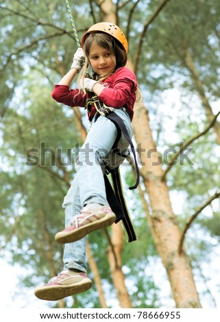 Girl climbing in forest - stock photo