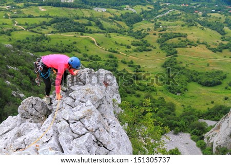 Girl climbing on limestone rocks high above ground - stock photo