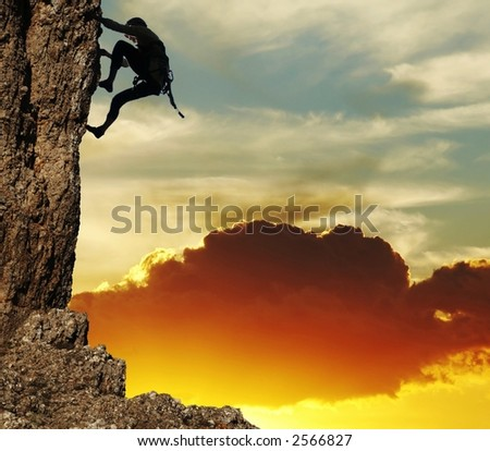 girl climbing on the rock on sunset background - stock photo
