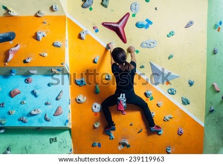 Girl climbing up on practice wall indoor, rear view - stock photo