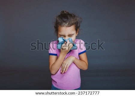girl closed her eyes and blowing his nose into a handkerchief - stock photo