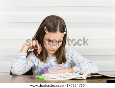 Girl concentrated on doing homework at home - stock photo