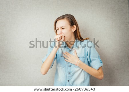 girl coughs and covers her mouth with his fist - stock photo