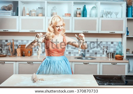 Girl cries in the kitchen, her hands stuck to the dough. She did not know how to cook dinner. - stock photo