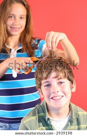 girl cutting boys hair vertical - stock photo