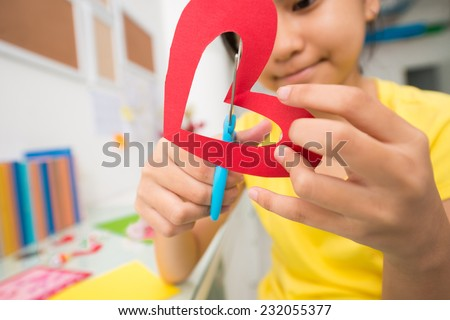 Girl cutting out paper heart, selective focus - stock photo