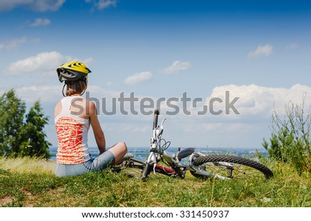 Girl cyclist with bycicle relax in the meadow - stock photo
