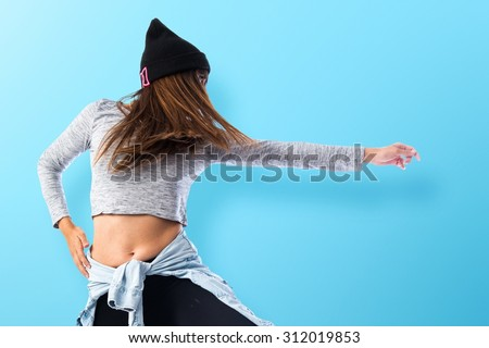 Girl dancing hip hop over colorful background - stock photo