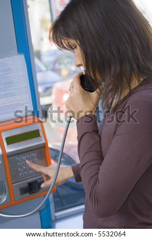 Girl dialing the number in a public phone cabin.Focus on the girl eye and hand. - stock photo