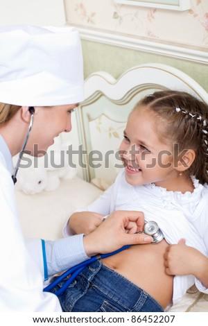 girl doctor listens to breathing - stock photo