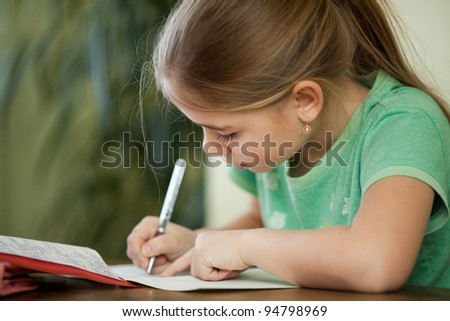 Girl does homework in her copybook. - stock photo