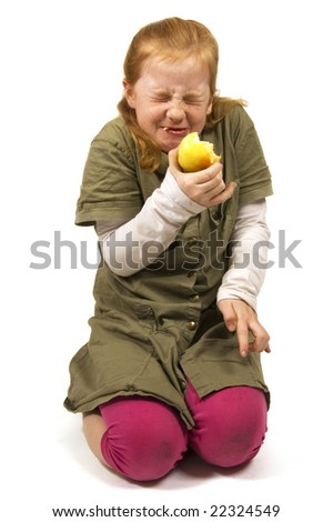 girl does not like the apple she is eating on white - stock photo