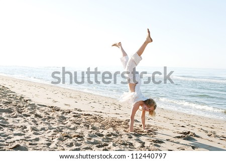Girl doing cartwheels on a golden sand beach near the shore, smiling happy. - stock photo
