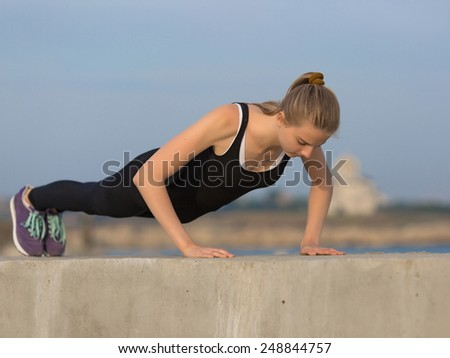 Girl doing exercises on open air. Young woman doing push ups outdoors.  - stock photo