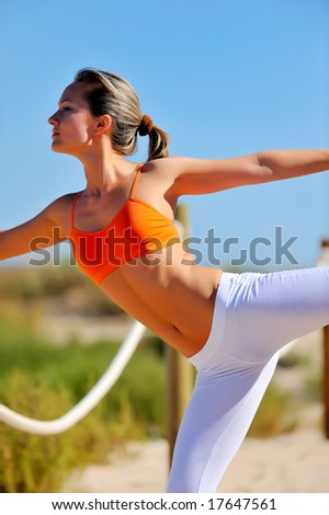 girl doing exercises on the beach at sunrise - stock photo