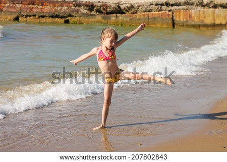 Girl doing gymnastics at the sea shore - stock photo