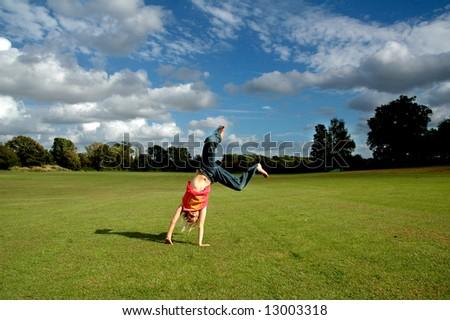 girl doing handstand in park - stock photo