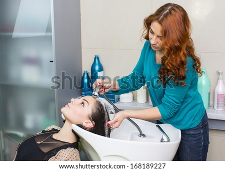 girl doing her hair in a beauty salon - stock photo
