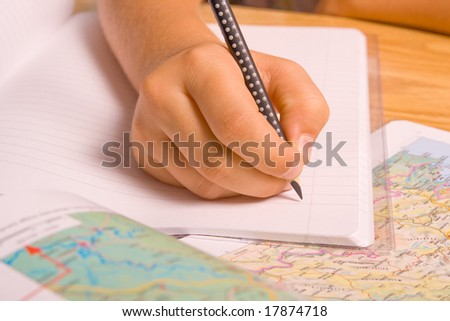 Girl doing her homework by writing in notebook. - stock photo