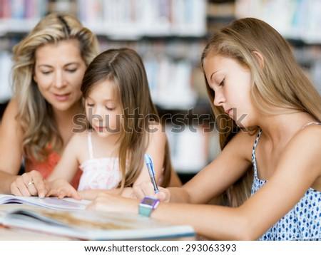Girl doing her homework in library - stock photo